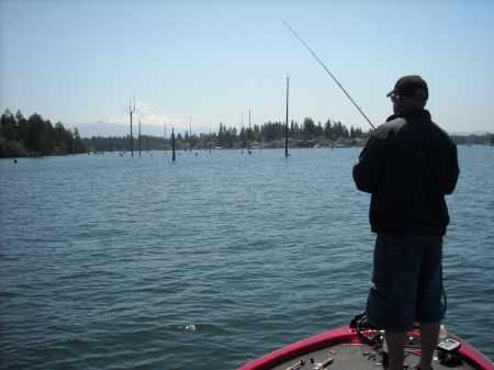 MT. RAINIER LOOMS BEHIND A DROWNED FOREST AS BASS ANGLER RANDY LEININGER WORKS A JIG BACK TO THE BOAT. (ANDY WALGAMOTT)