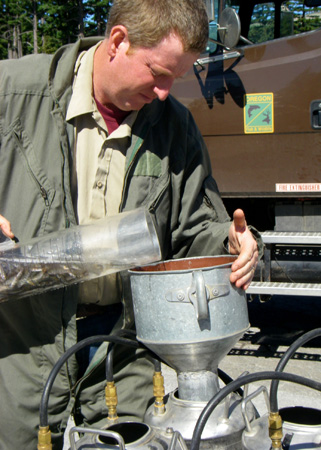 A TECH POURS TROUT FRY INTO A CANNISTER. (JULY 2007, ODFW)